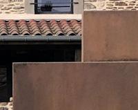 PP03 — Portail avec ouverture automatisée en bloc corten sur-mesure pour une maison de village dans la Loire.