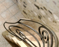 R03 — Rampe d'intérieur débillardée sur une moitié d'ovale, les courbes s'entrecroisent en petites grilles en trou renflé. Les marches de l'escalier en pierre sont prolongées en tôle afin de donner plus de mouvement à la rampe. Reys-de-Saulce (26)